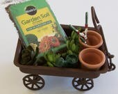 Miniature rusty wagon with potting soil, garden tools and succulents