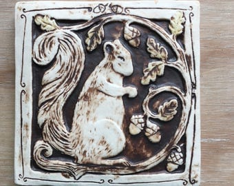 Handmade ceramic squirrel tile with a brown wash and light olive detail