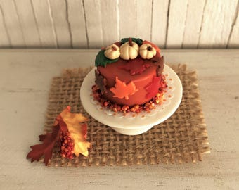 Miniature Cake In Pretty Fall Colors With White Pumpkins, Maple Leaves, and Berries