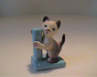 Vintage miniature Hagen Renaker Siamese kitten on blue scratch pad