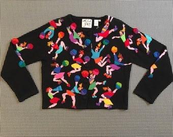 1998, black cardigan, with colorful, felt, cheerleaders, by Michael Simon, Women's size Medium