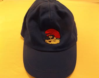 Hat child's with papa smurf embroidered on it.