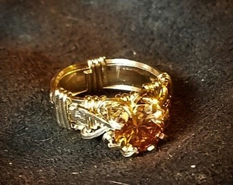 Beautiful Dark Champagne color CZ is set in yellow gold on a floral patterned band.  Wraps and band are 20/14 gold filled.  Ring size 5  1/2