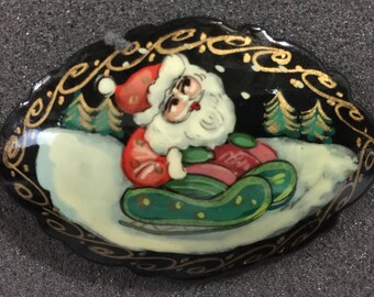 Vintage hand painted Santa riding on a sled pin hand made in Russia