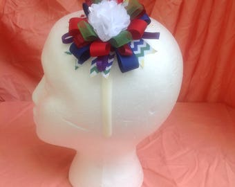 White headband with multi color now and white flower in the center
