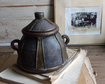 Old  shabby clay pot with brass ornaments and lid