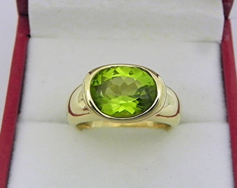 AAAA  Peridot Apple Green 3.32 carats  11x9mm in 14K Yellow gold bezel set ring. 0260