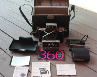 Vintage Polaroid 360 camera outfit include Electronic , detachable flash, Charger, leather carrying case, instruction manual and cold clip.
