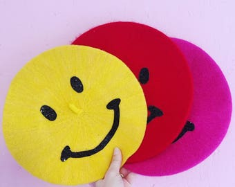 Smiley face yellow red pink beret hat.