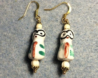 Off white, orange, green and black ceramic lemur bead earrings adorned with off white Czech glass beads.