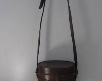 Vintage oval brown leather shoulderbag with strap and clip closure.