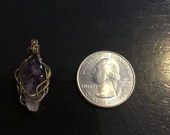 Small wire wrapped amethyst stone. Made with gold and silver colored wire.