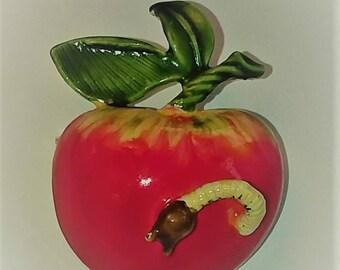 Humorous worm in apple pin.
