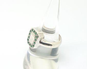 Silver ring with green zirconium gemstones.