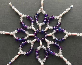 Eight-pointed star of sparkling violet and transparent crystals. An exquisite decoration for a Christmas tree. A gift for loved ones.