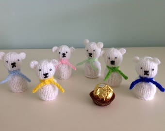 Polar bears hand knitted to cover a Ferrero Rocher chocolate or similar.