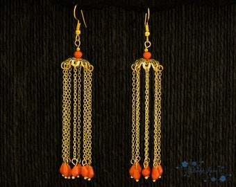 Long earrings made with chains plated in gold and orange glass beads