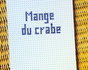 "Book ""eat crab"" embroidered in cross stitch"