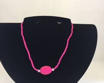 Simple yet striking hot pink bead necklace with subtle oval feature bead.