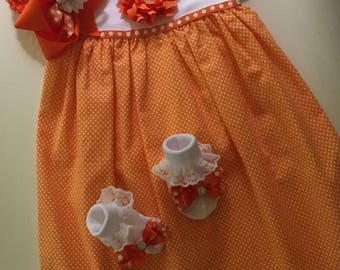 Girls 3-9 mo. Onesie dress, short sleeved bright orange with coordinating headband and socks.