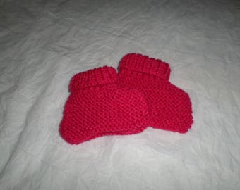 pair of booties with pink acrylic yarn