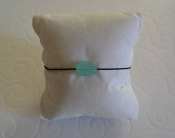 Pillows with sea green cord bracelet