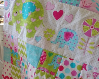 Cot quilt for baby girl with elephant appliqué.