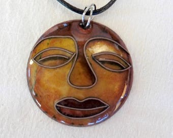 Necklace in Brown and gold, compartmentalized enamels African face in copper wire, black cord.