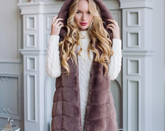 The waistcoat from Jekomeha under a mink a cross-section with a hood is light-brown.