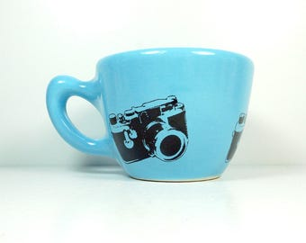 a 12oz cup glazed in Cloudless Blue with Leica camera prints READY TO SHIP