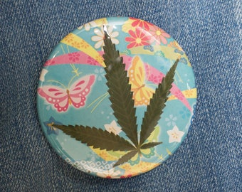 Pressed Cannabis Leaf Button on Turquoise, PInk & Yellow Background
