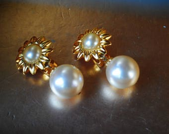 Classy vintage 80s gold tone metal , sunflower shape  clip on earrings with a large , white ,faux ,dangle pearl. Made by Maeve Carr.
