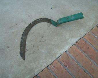 old green handle hand scythe farm tool