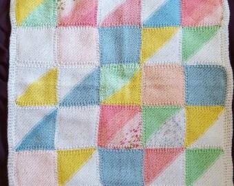 Knit baby cot blanket in patchwork design