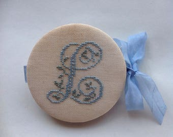 "Primitive cross stitched needle case with monogram letted ""L"" in soft blue"
