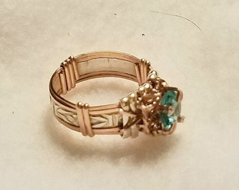 Outstanding Natural blue zircon,  6mm round cut, is set on a narrow sterling silver band with rose gold rims and prongs.  Size 4