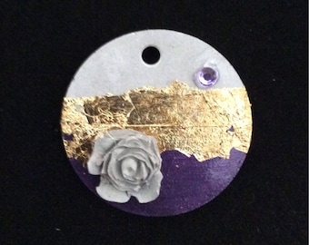 Pendant in concrete, around versieerd, with a rose in concrete, a rhinestone and gold leaf