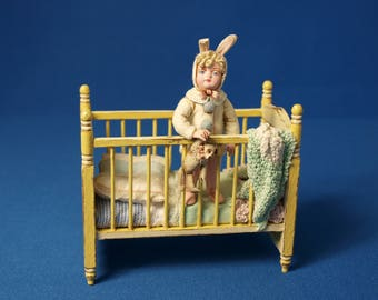 12th scale model of a child in a cot