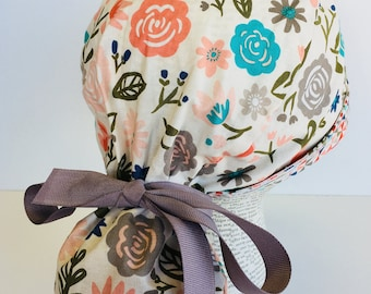 Ponytail Scrub Cap scrub hat featuring a beige material with flowers in peach teal and green with a coordinating band 2t