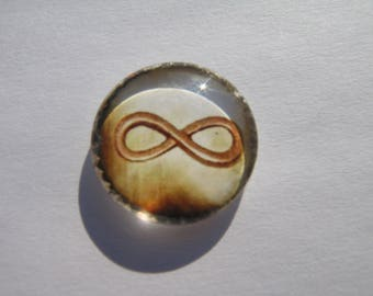 Cabochon 20 mm with a drawing of the infinity sign on a beige Brown background