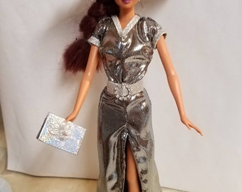 Barbie clothes, silver slinky dress with slit up front. Belt with bling buckle, hat with silver tinsel trim, purse, white shoes.