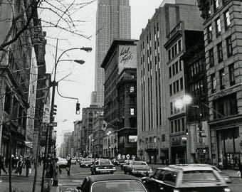Empire State 70's is a retro black and white early springtime scene of the Big Apple and the Empire State Building and old cars in 1978