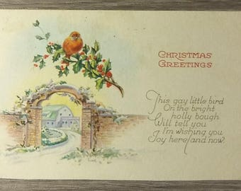 Vintage Christmas Greetings 1924 postcard feat. a red bird on a bough of holly over a gate with a house in the background, 1-cent stamp