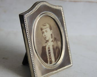 Silver-colored photo frame with old photo of a young girl (1883)