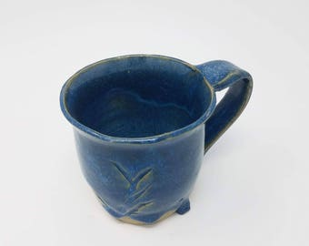 Small  handmade blue mug with drip and carve.
