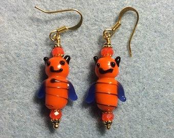 Orange and dark blue lampwork honeybee bead earrings adorned with orange Chinese crystal beads.