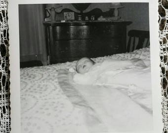 Vintage snapshot of a Sleeping baby on bed or possible post mortem