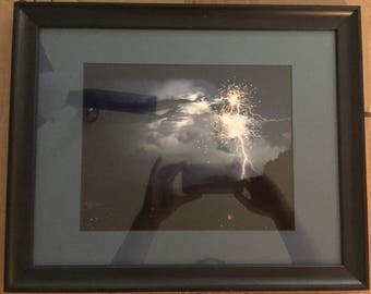 Framed photograph of fireworks during lightning storm