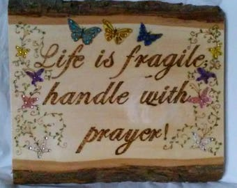 """Wood burned painted and embellished plaque with butterflies and vines, and an inspirational saying """"Life is fragile; handle with prayer""""."""