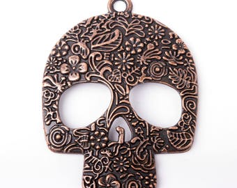 Skull shaped pendant, decorated with flowers, copper
